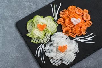 Figured slicing vegetables for vitamin salad to Valentine's Day