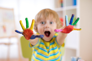 Cheerful child boy showing hands painted in bright colors. Focus on color palms