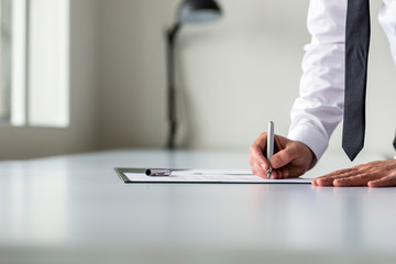 Man in white shirt signing contract or subscription form