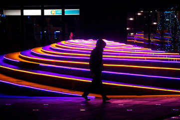 A man walks past Christmas decorations in front of an office building in Beijing