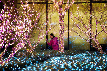 A girl walks past Christmas decorations in front of an office building in Beijing