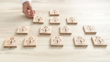 Human resources concept with a businessman arranging a series of wooden blocks