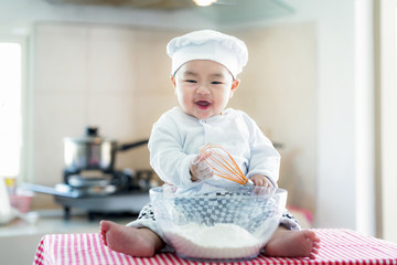 Asian baby in kitchen, newborn baby concept for job, career, occupation and dream. Food, cooking, bread and bakery concept