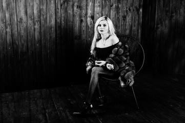 Elegante blonde girl wear on fur coat sitting on chair at studio against wooden background.