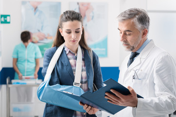 Professional doctor with a female patient with broken arm and nurse working on the background