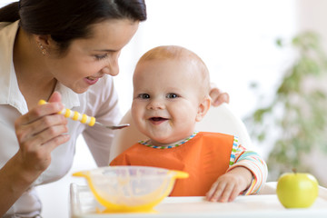 Mother feeding her baby with spoon. Mother giving healthy food to her adorable child at home
