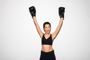 Happy screaming curly brunette fitness woman rejoices