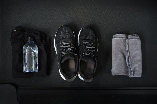 Top view of black tone fitness accessories  on treadmill background , running concept