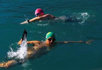 Swimmer Gewert holds a log found on the lake during their 70 km relay near Le Bouveret