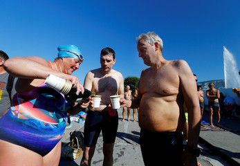 Swimmers Gewert, Naunton and Whitehead celebrate after swimming a 70 km relay across Lake Leman at Bains des Paquis in Geneva