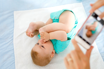 Parent taking photo of a baby with smartphone. Adorable newborn child taking foot in mouth