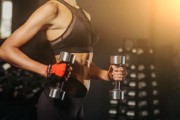 Spoed Foto op Canvas Fitness woman in black elegancy sportwear holding in hands dumbbell. Girl posing in fitness club.