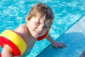 Happy little kid boy having fun in an swimming pool