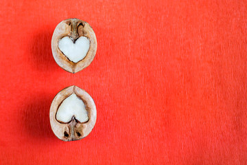 Two halves of walnut in shape of heart are lying over one another on red textured paper.
