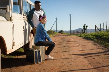 Couple sitting on suitcase at countryside