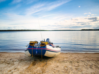 Inflatable fishing boat with fishing equipment on the lake coast line in the evening
