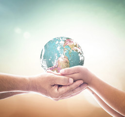 International human solidarity day concept: Human hands holding earth global on blurred nature background. Elements of this image furnished by NASA