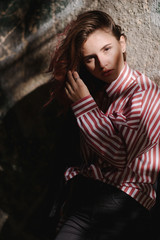 Portrait of young beautiful girl wearing stylish shirt, black skinny jeans, glasses. Girl have shinny long red hair. Female fashion concept