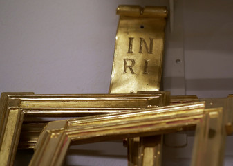Gold-plated picture frames and a christian cross inscription are seen at Arte Aurelia gold-plating workshop in Vienna