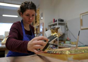 A craftswoman applies gold leaf on picture frame at Arte Aurelia gold-plating workshop in Vienna