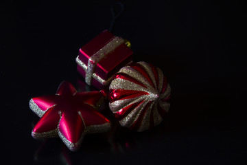Red-gold Christmas baubles on a black background