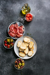 Canvas Prints Assortment Ingredients for making tapas or bruschetta. Crusty bread, ham prosciutto, sun dried tomatoes, olive oil, olives, pepper, greens on plates over dark texture background. Top view with space