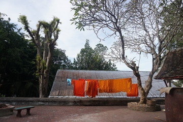 Orange cloths of monks in Laos city in backyard of a pagoda