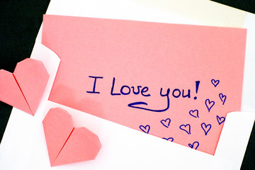 Letter with text I Love You! in envelope and two pink origami hearts.