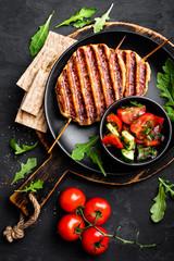 Juicy grilled chicken meat lula kebab on skewers with fresh vegetable salad on black background, top view