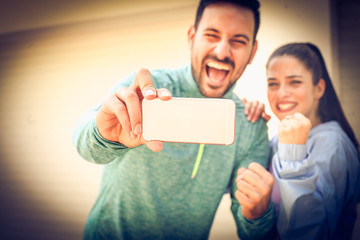 Young smiling couple making selfie on street after running.