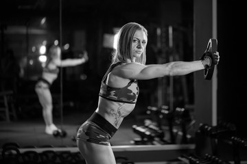 Beautiful bodybuilder woman with lifting dumbbells. Sporty girl showing her well trained body. Well-developed muscles by strength training. black and white