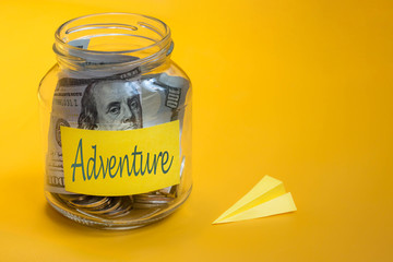 Travel budget concept. Money saved for vacation in glass jar on orange background, copy space. Paper airplane, Banknotes and coins for adventure