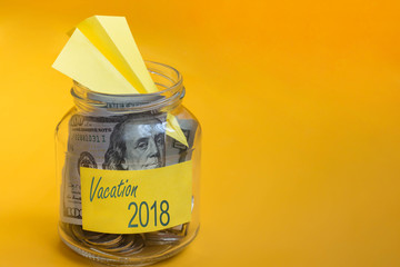 Coins, paper airplane and dollars in glass jar with vacation 2018 label on orange background. Saving money for travel, planning holiday or vacation. Copy space