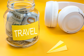 Saving money for travel concept. Money savings in a glass jar on desk work with paper airplane and headphones