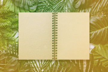 summer ideas concept with tropical leaf frame border on white vintage wooden background with blank page notebook with recycle paper