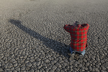 Desperate man kneeling and holding his head in his hands at dry cracked land after drought, natural disaster