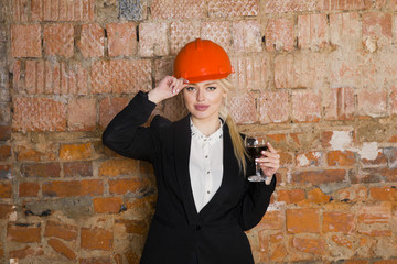 Portrait of architect student or painter with glass of wine and protect helmet wearing. Brick red background.