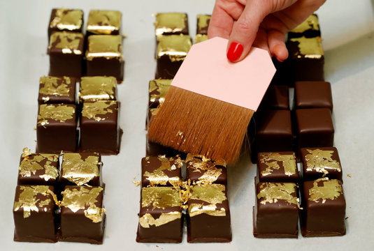 Confectioner Schmid of Wenckeschmid patisserie uses a brush to place gold leafs on Petit Fours D'or chocolates in Basel