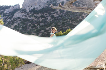 Bride in nature in the mountains near the water. Dress color Tiffany. The bride is playing with his dress.