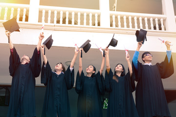 Graduating Students holding their diploma and throwing Caps in the Air
