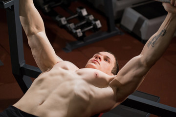 Brutal athletic man pumping up muscles on bench press