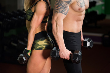 Beautiful young sporty sexy couple showing muscle and workout in gym