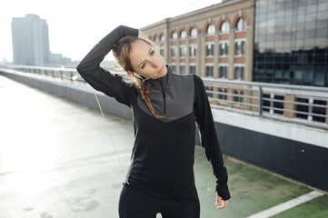 Blonde woman stretching neck before urban workout at rooftop in the morning