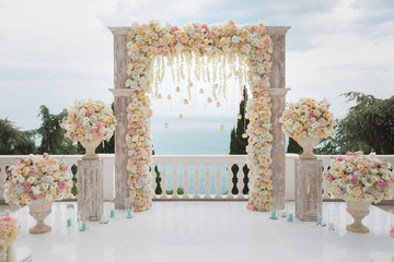 Elegant wedding arch with fresh flowers, vases on background of ocean and blue sky. Fotomurales