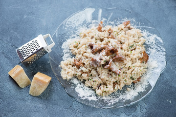 Risotto with chanterelles and parmesan cheese on a blue stone background, studio shot