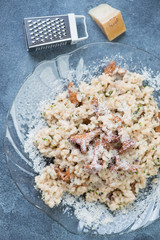 Top view of risotto with chanterelle mushrooms on a blue stone surface, vertical shot