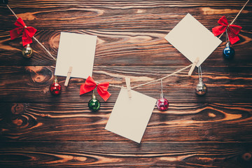 White notes on wooden background with christmas decor