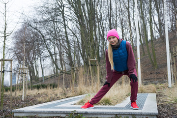 Sporty girl stretching outdoor in park.