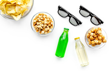 Fast food for watching film. Crisps, popcorn, rusks near drink and glasses on white background top view copyspace