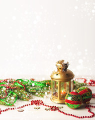 Christmas balls, decorations on a wooden background with spruce branches and a flashlight.